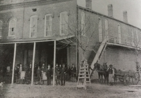 Jesse P. Norfleet (standing, left of right column), outside his store on the Square.